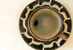 Um copo do preto fabricou cerveja em um café do cezve em uns pires Imagem de Stock
