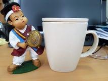 Um copo um café e uma estátua pequena Fotos de Stock Royalty Free