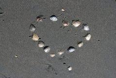 Um coração com escudos na areia Fotografia de Stock Royalty Free