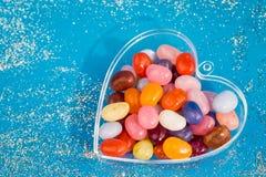 Um coração com os doces no fundo azul imagem de stock royalty free