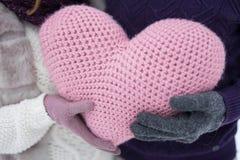 Um cora??o cor-de-rosa grande nas m?os de um homem e de uma mulher imagens de stock royalty free