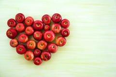 Um coração das maçãs vermelhas maduras no fundo de madeira verde Fotos de Stock Royalty Free