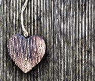 Um coração de madeira do vintage em pranchas da madeira do grunge. Amor Foto de Stock
