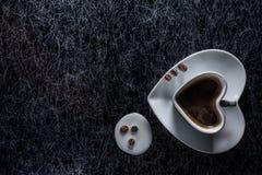 Um coração deu forma ao copo de café com feijões de café e derramou o leite em um tampo da mesa de prata do fundo da cozinha fotos de stock