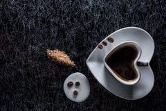 Um coração deu forma ao copo de café com feijões de café, leite derramado e açúcar mascavado em um fundo preto com fresta de espe fotos de stock royalty free