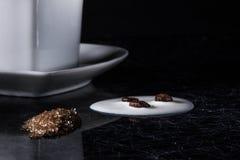 Um coração deu forma ao copo de café com feijões de café, leite derramado e açúcar mascavado em um fundo preto com fresta de espe imagem de stock royalty free