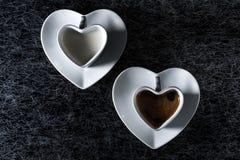 Um coração deu forma ao copo de café e ao copo do leite com café preto em um fundo preto com fresta de esperança fina imagens de stock royalty free