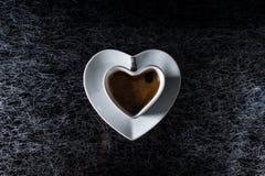 Um coração deu forma ao copo do coffe com café preto em uma parte superior do preto e de mesa de cozinha do fundo da prata fotos de stock royalty free