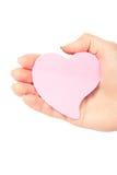 Um coração do cartão está em uma mão Fotografia de Stock Royalty Free