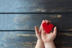 Um coração vermelho guardou por dois punhos do ` s das crianças em um backgroun de madeira Fotografia de Stock