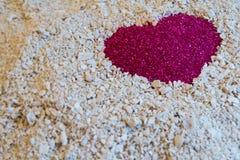 Um coração vermelho na areia na areia branca do coral Fotografia de Stock