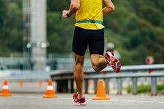 Um corredor atlético masculino que corre nas estradas com segurança dos cones do tráfego Imagem de Stock
