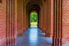 Um corredor de um forte de Rajasthan com as paredes bricked vermelhas e entrada arqueada Na extremidade da entrada é uma família  foto de stock royalty free