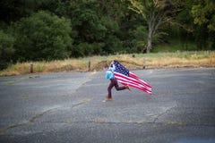 Um corredor novo do menino ao guardar a bandeira americana que mostra o patriotismo para seu próprio país, une estados fotografia de stock