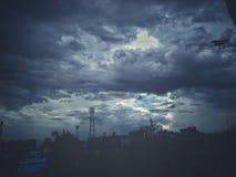 Um corvo pequeno em uma cidade tormentoso do céu azul Imagens de Stock Royalty Free