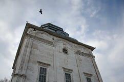 Um corvo que voa sobre um templo com paredes rachadas Fotografia de Stock Royalty Free
