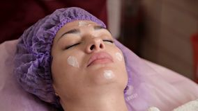 Um cosmetologist da mulher aplica um creme terap?utico especial ? cara do paciente Pele limpa, cuidado vídeos de arquivo