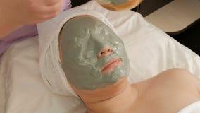 Um cosmetologist profissional aplica uma máscara do alginate na cara de uma mulher adulta da aparência Rejuvenescendo o procedime filme