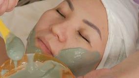 Um cosmetologist profissional aplica uma máscara do alginate na cara de uma mulher asiática Close-up Rejuvenescendo o procediment video estoque