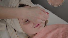 Um cosmetologist profissional aplica uma máscara protetora a uma moça com uma escova Novo conceito na cosmetologia video estoque