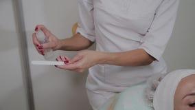 Um cosmetologist profissional desinfeta o instrumento com uma solu??o especial Inova??es de Cosmetological video estoque