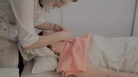 Um cosmetologist profissional faz um procedimento da massagem de cara antes de aplicar uma máscara Novo conceito na cosmetologia filme