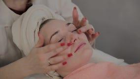 Um cosmetologist profissional faz um procedimento da massagem de cara antes de aplicar uma m?scara Novo conceito na cosmetologia video estoque