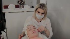 Um cosmetologist profissional fricciona a cara da menina com as limpezas hidratando especiais Novo conceito na cosmetologia vídeos de arquivo