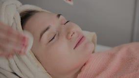 Um cosmetologist profissional fricciona a cara da menina com as limpezas hidratando especiais Novo conceito na cosmetologia video estoque