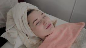 Um cosmetologist profissional fricciona a cara da menina com as limpezas hidratando especiais Novo conceito na cosmetologia filme
