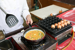 Um cozinheiro chefe está cozinhando uma omeleta Foto de Stock Royalty Free