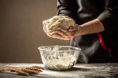 Um cozinheiro chefe experiente em uma cozinha profissional prepara a massa com farinha para fazer a bio massa italiana o conceito foto de stock
