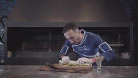 Um cozinheiro chefe experiente no uniforme azul e nas luvas brancas do cozinheiro chefe envolve o enchimento de dar água na boca  vídeos de arquivo