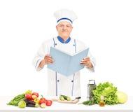 Um cozinheiro chefe maduro que lê um livro de receitas durante uma preparação da salada Fotografia de Stock Royalty Free