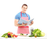 Um cozinheiro chefe masculino que lê um livro de receitas ao preparar uma salada Fotografia de Stock Royalty Free