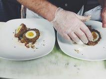 Um cozinheiro chefe Preparing um prato bonito de ovos escoceses fotos de stock
