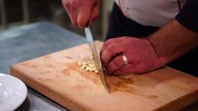 Um cozinheiro chefe que desbasta o alho em uma placa de corte Um alimento do corte do homem Homem que desbasta o alho com faca video estoque