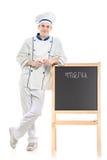 Um cozinheiro chefe que levanta perto da placa Imagens de Stock Royalty Free