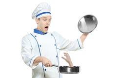 Um cozinheiro chefe supsised que prende uma frigideira Fotos de Stock