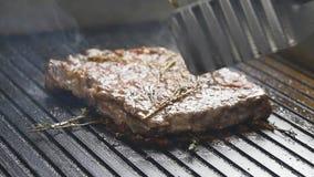 Um cozinheiro gerencie acima de um bife da carne em uma grade no movimento lento video estoque
