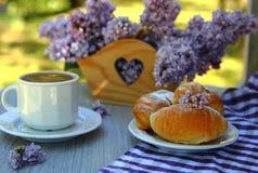 Um croissant com um ramalhete dos lilás e da xícara de café foto de stock royalty free
