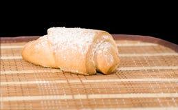 Um croissant doce está na esteira da palha Imagem de Stock Royalty Free