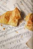 Um croissant em papéis velhos Imagem de Stock Royalty Free