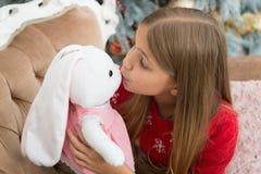 Um cutie kissable Brinquedo pequeno do coelho do beijo da menina Menina com o coelho bonito na árvore de Natal Pouca brincadeira  foto de stock royalty free