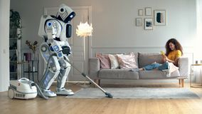 Um cyborg hoovering uma sala com uma senhora nela filme