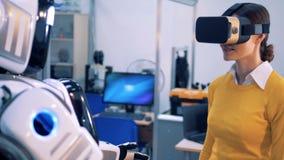 Um cyborg vem a uma mulher e toma-lhe as mãos Conceito do jogo da realidade virtual vídeos de arquivo
