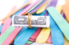 Um dólar Bill Rolled em um elástico no foco Fotografia de Stock Royalty Free