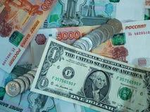 Um dólar e diversas contas em mil e cinco mil rublos de russo e moedas, close-up Foto de Stock