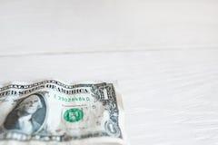 Um dólar no fundo de madeira branco, espaço livre Imagem de Stock