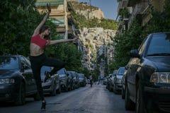 Um dançarino fêmea da aptidão bonita nova está levantando na rua do estreito da cidade na noite do verão na frente do monte alto fotos de stock